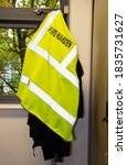 Small photo of Manchester, United Kingdom - 17th Oct 2020: Fire Warden Hi Vis yellow reflective vest hanging on a coat stand in a work office.