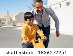 Small photo of Cheerful middle eastern father helping excited son to ride wooden balance cycle on street. Happy boy enjoying riding bycicle with his dad. Dad teaching his indian son to ride bicycle outdoor.