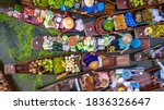 Small photo of Aerial view famous floating market in Thailand, Damnoen Saduak floating market, Farmer go to sell organic products, fruits, vegetables and Thai cuisine, Tourists visiting by boat, Ratchaburi, Thailand