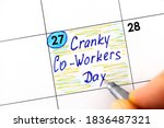 Small photo of Woman fingers with pen writing reminder Cranky Co-Workers Day in calendar. October 27