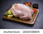 Small photo of Raw whole chicken with skin arranged on wooden board and garnished with parsely,small tomato,spring onion,chilli flakes and lemon slices with stone textured colour as background ,isolated