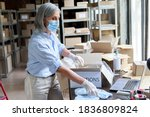 Small photo of Mature female volunteer warehouse worker wearing face mask working in shipping delivery charitable stock organization packing medical donations box. Covid 19 coronavirus donating and volunteering.