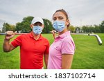 Small photo of Two modern golfers in disposable face masks and polo shirts standing on the golf course