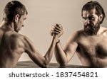 Small photo of Arms wrestling thin hand, big strong arm in studio. Two man's hands clasped arm wrestling, strong and weak, unequal match. Heavily muscled bearded man arm wrestling a puny weak man.