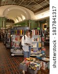 Small photo of 2020.09.06 St. Petersburg, Russia, Dom Knigi, Dom Zinger giant bookstore in landmark building. Young girl chooses a book.