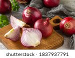 Small photo of Purple Onions. Fresh whole purple onions and one sliced onion on a stone countertop.