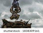 An Excavator Loads Scrap Metal...