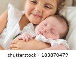 girl holding her newborn...   Shutterstock . vector #183870479