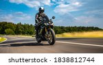 Small photo of motorbike on the road riding. having fun driving the empty road on a motorcycle tour journey. copyspace for your individual text. Fast Motion Blur effect
