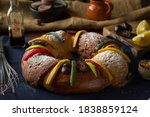Small photo of Mexican traditional rosca de reyes with fig, orange, Oaxaca chocolate and powdered sugar with a clay jarrito on a jute sack in the background for the dia de los Reyes Magos celebration on january 5th