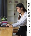 Small photo of Young beautiful female office worker working with digital abet on wooden bar in cafe