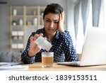 Small photo of Indian woman sit at office desk touch head pouring into glass of water anti hangover powder revival remedy. Abuse excessive alcohol consumption, seasonal grippe virus treatment need sick leave concept