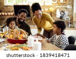 Small photo of Happy black family having roast turkey for lunch while celebrating Thanksgiving at home.