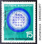 Small photo of MADRID, SPAIN - SEPTEMBER 13, 2020. Vintage stamp printed in Germany shows 25 years of nuclear fission, Hahn and Strassmann image of the nuclear reactor, progress in science and technology
