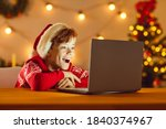 Small photo of Happy surprised child looking at laptop computer screen lighting up his face, seeing wonderful Christmas gifts and amazing presents in Internet store or watching online Xmas film on cinema website