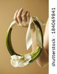Arty wedding bouquet made of white orchids like a ring with beige ribbon. Daylight. Studio shot - stock photo