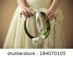 Arty wedding bouquet made of white orchids like a ring with beige ribbon. Daylight. Close up. Studio shot - stock photo