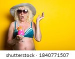 Old woman in a swimsuit with a hat holding a cocktail in surprise on a yellow background. - stock photo