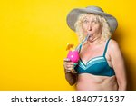 Old woman in a swimsuit in a hat in surprise drinks a cocktail on a yellow background. - stock photo