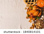 Fall thanksgiving table with roasting chicken or turkey, nuts, pie, pumkins and other food on light tablecloth, rustic, top view