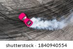 Small photo of Aerial top view professional driver drifting car on asphalt road track with white smoke, Automobile race car drift on abstract asphalt road with black tire skid mark, View from above.