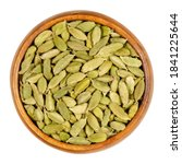 Small photo of Green cardamom pods in a wooden bowl. True cardamom, processed pods and seeds of Elettaria cardamomum, sometimes cardamon or cardamum, used as a spice. Close-up, from above, isolated macro food photo.