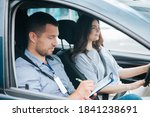 Small photo of Learning to drive a car. Male instructor and female student practicing in driving. Young man notice results of test in his paper. Cheerful woman satisfied with driving lessons.