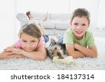 siblings lying on rug with... | Shutterstock . vector #184137314