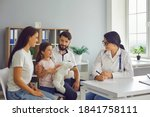 Small photo of Happy family with child in pediatrician's office consulting friendly young female doctor. Mother, father and daughter talking to supportive paediatrician during regular check-up in modern hospital