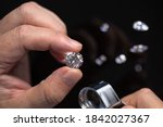 Small photo of Round shape diamond in hands of jeweller. Man jeweller examines a diamond. Gem grading and checking. Diamond business.