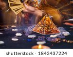 Small photo of Magic divination and esotericism. Magic glass pyramid with a magical glow. In the background, a fortune teller holds a fan of Tarot cards. Close-up of hands
