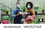 Small photo of Portrait of joyful African American male and female in masks standing in flower shop and holding Open sign. Woman and man florists workers looking at camera in good mood. Family business concept