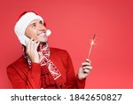 Small photo of Smiling man in santa hat holding sparker while talking on smartphone isolated on red