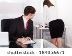 Small photo of Young pervert businessman looking at businesswoman working in office
