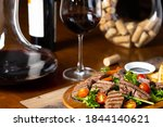 close up of grilled beef tenderloin fillet with rocket salad and cherry tomatoes pairing with Italian fine red wine bottle, glass and decanter in a wooden table classic vintage elegant moody style