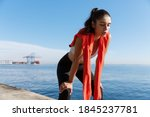 Outdoor shot of tired fitness woman panting and taking a breath after jogging, standing on a pier with sea behind her