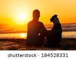Stock photo relaxed woman and dog enjoying summer sunset or sunrise over the sea sitting on the sand at the 184528331