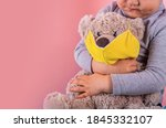 Toddler boy hugging toy Teddy bear wearing yellow mask on its face. Copy space. Concept of protecting children during a pandemic. - stock photo