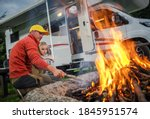 Recreational Vehicle RV Camper Camping and Family Time. Caucasian Father and His Daughter Hanging Next to Campfire on Their RV Park Pitch. Class C Motorhome in Background. - stock photo