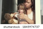 mom and daughter are playing on windowsill, dressing teddy bear with protective mask from viruses, looking out window. family child and mother in home quarantine. child hugs toy. Covid 19 coronavirus - stock photo