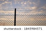 Barb Wire Fence Against Dusk