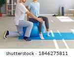 Small photo of Cropped low section of young woman sitting on stability ball in physio room of medical center doing physical exercise for healthy fit back with professional physiotherapist or chiropractor helping her