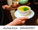 The Waiter Holds A Plate Of...