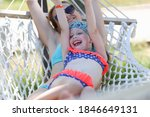 Woman And Girl Lie In Hammock...