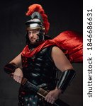 Small photo of Handsome and warlike legionary in black armour with red cape and helmet poses with sheathed sword in dark background.