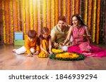 Small photo of Indian family lighting or arranging oil lamp or diya around flower rangoli on diwali festival night