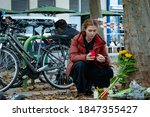 Small photo of Vienna, Austria - 03 November 2020. Woman lays flowers in mourning over the victims of the previous nights terror attack in the city centre.