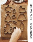 Small photo of Hands cutting gingerbread dough with festive metal cutters on rustic table flat lay. Person making Christmas gingerbread cookies, holiday advent