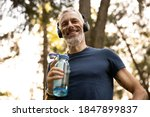 Small photo of Low angle portrait of joyful grizzled athletic male drinking water while doing workout in sunny forest