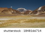 The Andes mountain range. Panorama view of the yellow meadow, the brown mountains, golden valley and Volcano Incahuasi, under a deep blue sky.